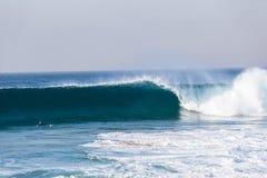 El practicar surf de batimiento no identificado de la persona que practica surf azul de la onda Foto de archivo