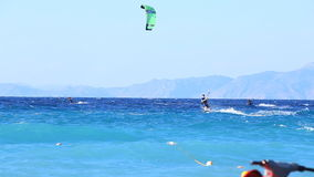 El practicar surf de la cometa - personas que practica surf en superficie azul del mar metrajes