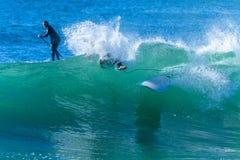 El practicar surf de la onda del Wipeout de la muchacha de la persona que practica surf que se estrella Foto de archivo libre de regalías