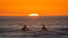 El practicar surf de la puesta del sol imagen de archivo libre de regalías