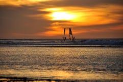 El practicar surf de la puesta del sol Imagenes de archivo