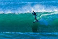 El practicar surf de pie del paseo de la onda del Paddler de la persona que practica surf Imagen de archivo libre de regalías