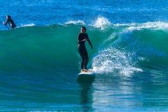 El practicar surf del paseo de la onda de la muchacha de la persona que practica surf Imágenes de archivo libres de regalías