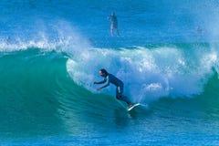 El practicar surf del paseo de la onda de la muchacha de la persona que practica surf Foto de archivo