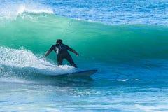 El practicar surf del paseo de la onda de la persona que practica surf Foto de archivo libre de regalías