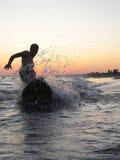 El practicar surf en la playa imagen de archivo libre de regalías
