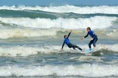 El practicar surf en la playa de Muriwai - Nueva Zelanda Foto de archivo