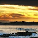 El practicar surf en la puesta del sol Fotos de archivo