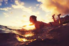 El practicar surf en la puesta del sol imagen de archivo