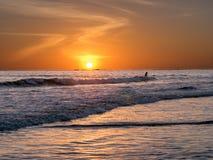 El practicar surf en la puesta del sol fotografía de archivo
