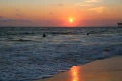 El practicar surf en la puesta del sol en la playa de Hermosa Imagenes de archivo