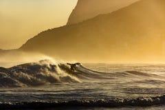 El practicar surf en la puesta del sol del verano Fotos de archivo