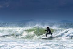 El practicar surf en la ruina en Byron Imágenes de archivo libres de regalías