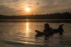El practicar surf en Maine en la puesta del sol imagen de archivo