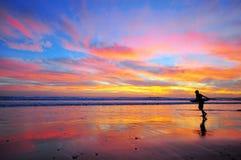 El practicar surf en puesta del sol Foto de archivo libre de regalías