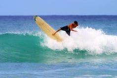 El practicar surf joven de Gavin de la persona que practica surf en la playa de Waikiki Imagen de archivo