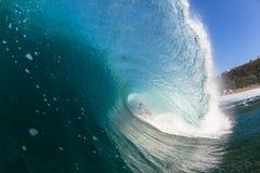 El practicar surf limpia hacia fuera la onda que se estrella hueco azul del interior Foto de archivo libre de regalías