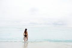El practicar surf que va de la muchacha de la persona que practica surf mirando la playa del océano Fotografía de archivo libre de regalías