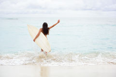 El practicar surf que va emocionado feliz de la muchacha que practica surf en la playa Fotos de archivo libres de regalías