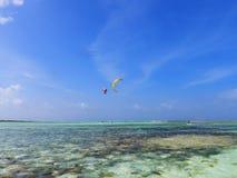 El practicar surf y viento que practican surf en el mar del Caribe, Los Roques, Venezuela de la cometa imagenes de archivo