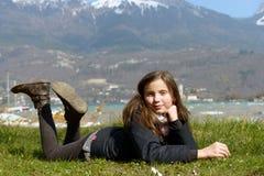 El preadolescente bonito está mintiendo en la hierba verde Foto de archivo libre de regalías