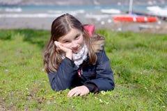 El preadolescente bonito está mintiendo en la hierba verde Fotografía de archivo