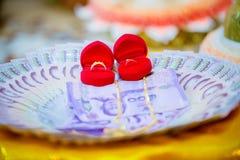 El precio de novia, los accesorios del oro para el novio y la novia en corazón de lujo de la caja forman en la bandeja en la boda Imagen de archivo