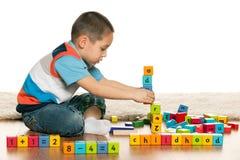 El preescolar listo está jugando con los juguetes Imagen de archivo libre de regalías
