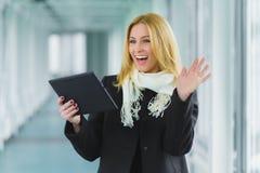El preguntarse y la mujer de negocios acertada se vistieron en la capa que miraba la tableta en pasillo Imagenes de archivo