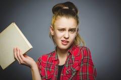 El preguntarse y muchacha subrayada con el libro Primer adolescente en fondo gris Fotos de archivo