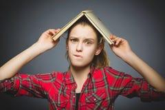 El preguntarse y muchacha subrayada con el libro Primer adolescente en fondo gris Foto de archivo