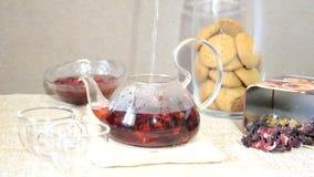 El preparar de proceso de la tabla roja de la porción del té para el desayuno, té rojo en tetera hojas de té, hibisco y dos tazas almacen de video