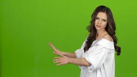 El presentador de la TV dice todo el mundo sobre el tiempo, ella es elegante y hermosa Pantalla verde almacen de video