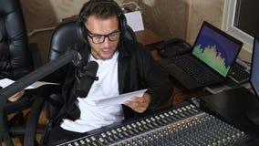 El presentador de radio masculino en las lentes con la hoja de papel habla en el micrófono cerca del equipo en el estudio de radi metrajes