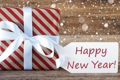 El presente con los copos de nieve, manda un SMS a Feliz Año Nuevo Imagen de archivo
