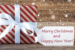 El presente con los copos de nieve, manda un SMS a Feliz Navidad y a Año Nuevo Foto de archivo libre de regalías