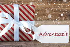 El presente con los copos de nieve, texto Advetszeit significa a Advent Season Fotografía de archivo libre de regalías