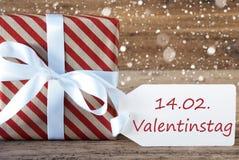 El presente con los copos de nieve, texto Valentinstag significa día de tarjetas del día de San Valentín Imagenes de archivo