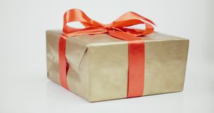 El presente envolvió con el papel de oro y ató el arco rojo de la cinta almacen de metraje de vídeo