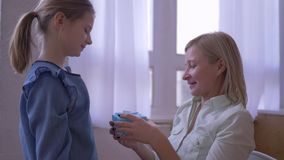 El presente a la madre, poca hija da el presente y abrazos sonrientes de cumpleaños de la mamá blando y disfruta en casa metrajes