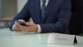 El presidente de la compañía usando el smartphone para la comunicación, viendo archiva en línea almacen de metraje de vídeo
