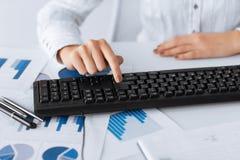 El presionado a mano de la mujer entra en el botón en el teclado Imagen de archivo