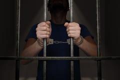 El preso arrestado está sosteniendo barras en celda de prisión Foto de archivo libre de regalías