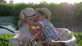 El primer amor, dos niños come manzanas y se divierte que se sienta en carretilla en el fondo de la puesta del sol en el campo almacen de video