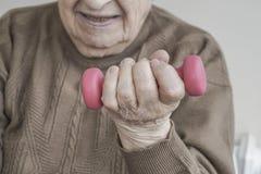 El primer arrugó la mano de una persona mayor que llevaba a cabo pesa de gimnasia Foto de archivo libre de regalías