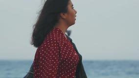 el primer asiático de la muchacha en una chaqueta negra va por el mar metrajes