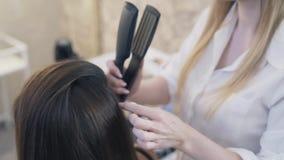 El primer, a cámara lenta un peluquero de la mujer hace un corte de pelo a un cliente que usa un ironer del pelo, prensando el pe almacen de video