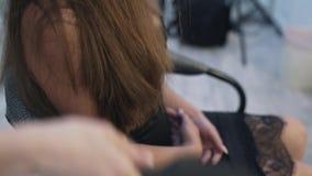 El primer, a cámara lenta un peluquero de la mujer peina el pelo largo a un cliente y los prepara para realizar procedimientos an metrajes