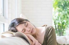El primer cansó sueño de la mujer después de que ella leyera un libro en el sofá en fondo texturizado sala de estar Fotografía de archivo libre de regalías