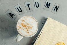 El primer Cappuccinoand redacta hola otoño y los wi amarillos del cuaderno Foto de archivo